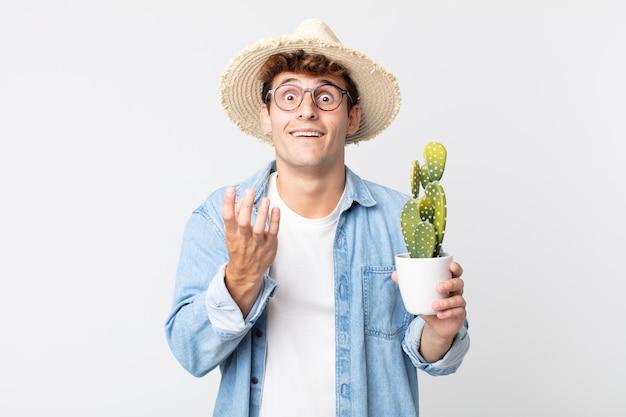 Hombre guapo joven que parece desesperado, frustrado y estresado. granjero sosteniendo un cactus decorativo