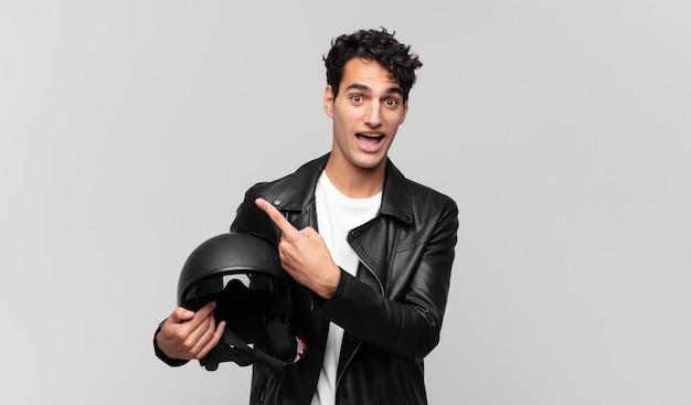 Hombre guapo joven que parece emocionado y sorprendido apuntando hacia un lado y hacia arriba para copiar el espacio. concepto de piloto de moto
