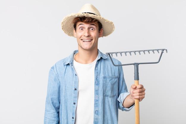 Hombre guapo joven que parece feliz y gratamente sorprendido. concepto de granjero