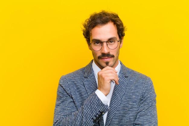 Hombre guapo joven que parece feliz y sonriente con la mano en la barbilla, preguntándose o haciendo una pregunta, comparando opciones contra naranja