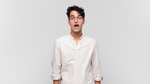 Hombre guapo joven que parece muy conmocionado o sorprendido, mirando con la boca abierta diciendo wow