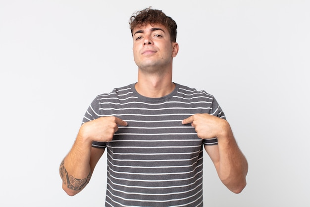 Hombre guapo joven que parece orgulloso, positivo y casual apuntando al pecho con ambas manos