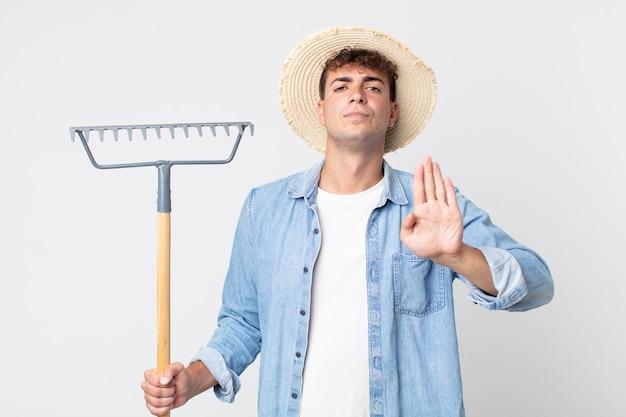 Hombre guapo joven que parece serio mostrando la palma abierta haciendo gesto de parada. concepto de granjero