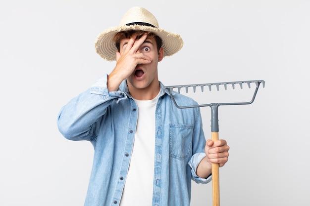 Hombre guapo joven que parece sorprendido, asustado o aterrorizado, cubriendo el rostro con la mano. concepto de granjero