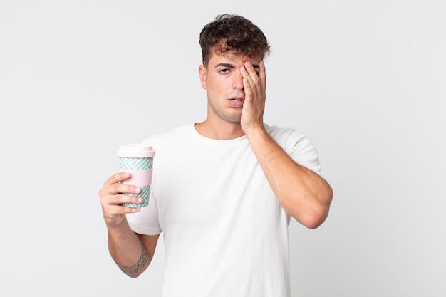 Hombre guapo joven que se siente aburrido, frustrado y con sueño después de un cansado y sosteniendo un café para llevar