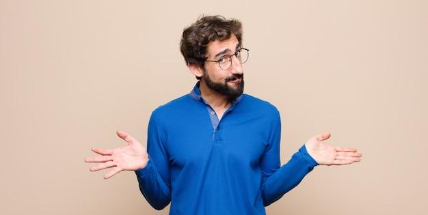 Hombre guapo joven que se siente confundido y confundido, inseguro sobre la respuesta o decisión correcta, tratando de tomar una decisión contra la pared plana