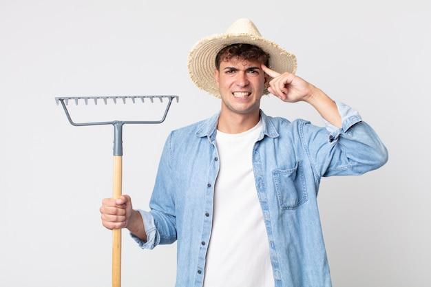 Hombre guapo joven que se siente confundido y desconcertado, mostrando que estás loco. concepto de granjero
