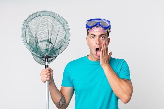 Hombre guapo joven que se siente conmocionado y asustado con gafas y red de pesca