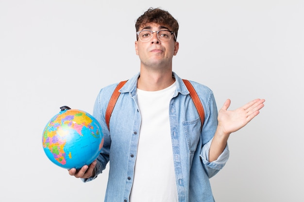 Hombre guapo joven que se siente desconcertado y confundido y dudando. estudiante sosteniendo un mapa del globo terráqueo