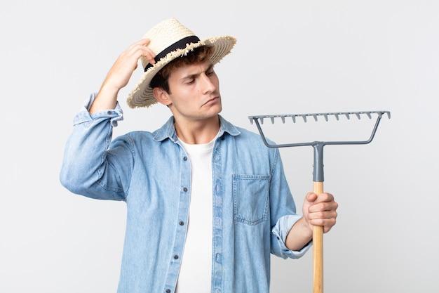 Hombre guapo joven que se siente desconcertado y confundido, rascándose la cabeza. concepto de granjero