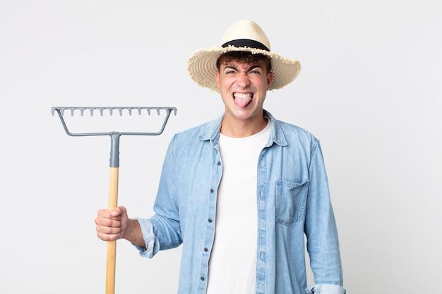 Hombre guapo joven que se siente disgustado e irritado y con la lengua fuera. concepto de granjero