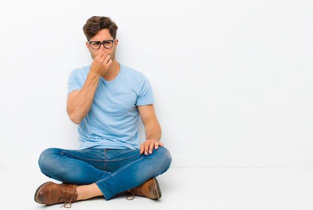 Hombre guapo joven que se siente disgustado, tapándose la nariz para evitar oler un hedor desagradable y desagradable sentado en el suelo