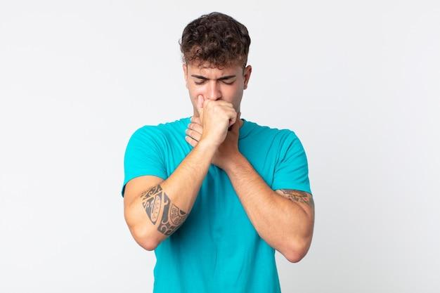 Hombre guapo joven que se siente enfermo con dolor de garganta y síntomas de gripe, tos con la boca cubierta
