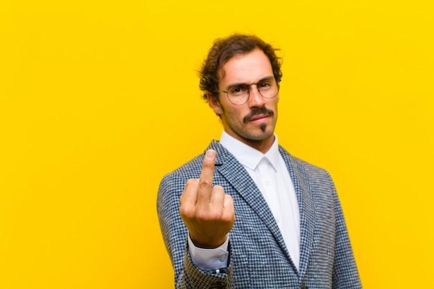 Hombre guapo joven que se siente enojado, molesto, rebelde y agresivo, moviendo el dedo medio, luchando