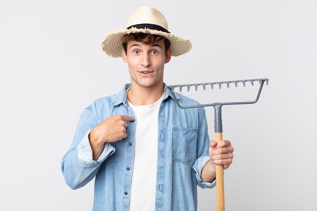 Hombre guapo joven que se siente feliz y apunta a sí mismo con un emocionado. concepto de granjero