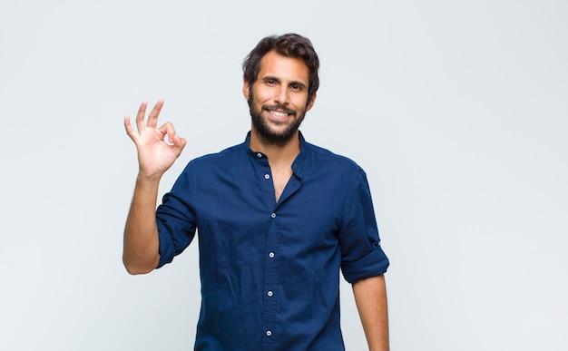 Hombre guapo joven que se siente feliz, asombrado, satisfecho y sorprendido, mostrando gestos bien y pulgares arriba, sonriendo