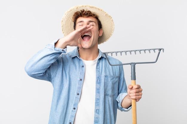 Hombre guapo joven que se siente feliz, dando un gran grito con las manos al lado de la boca. concepto de granjero