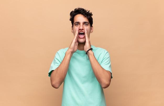 Hombre guapo joven que se siente feliz, emocionado y positivo, dando un gran grito con las manos al lado de la boca, gritando