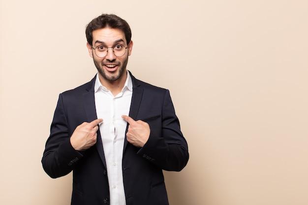 Hombre guapo joven que se siente feliz, sorprendido y orgulloso, señalando a sí mismo con una mirada emocionada y asombrada