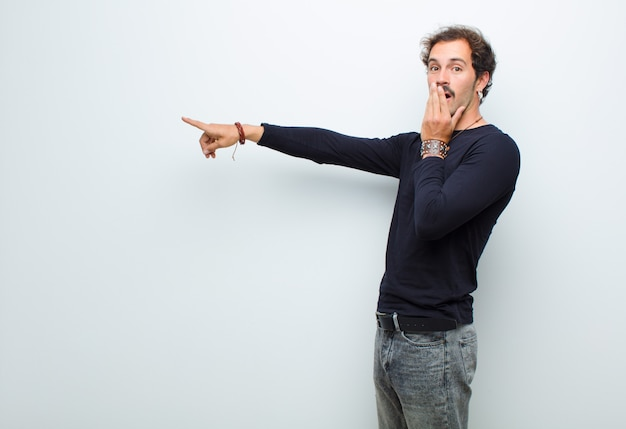 Hombre guapo joven que se siente feliz, sorprendido y sorprendido, cubriendo la boca con la mano y apuntando al espacio de copia lateral sobre la pared blanca