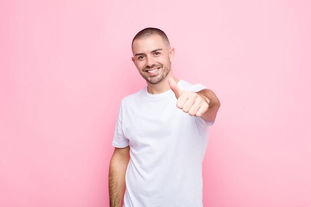 Hombre guapo joven que se siente orgulloso, despreocupado, confiado y feliz, sonriendo positivamente con los pulgares contra la pared plana