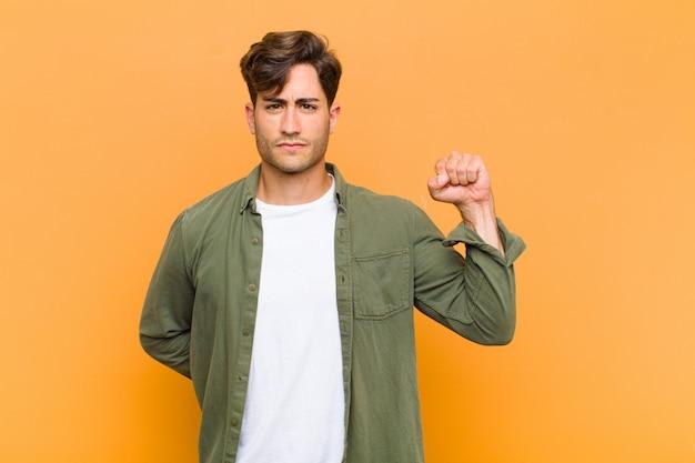 Hombre guapo joven que se siente serio, fuerte y rebelde, levantando el puño, protestando o luchando por la revolución contra el fondo naranja