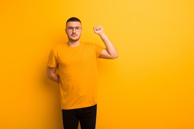 Hombre guapo joven que se siente serio, fuerte y rebelde, levantando el puño, protestando o luchando por la revolución contra la pared plana