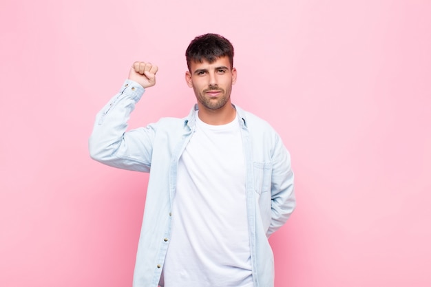 Hombre guapo joven que se siente serio, fuerte y rebelde, levantando el puño, protestando o luchando por la revolución contra la pared rosa