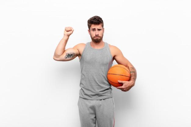 Hombre guapo joven que se siente serio, fuerte y rebelde, levantando el puño, protestando o luchando por la revolución sosteniendo una pelota de baloncesto