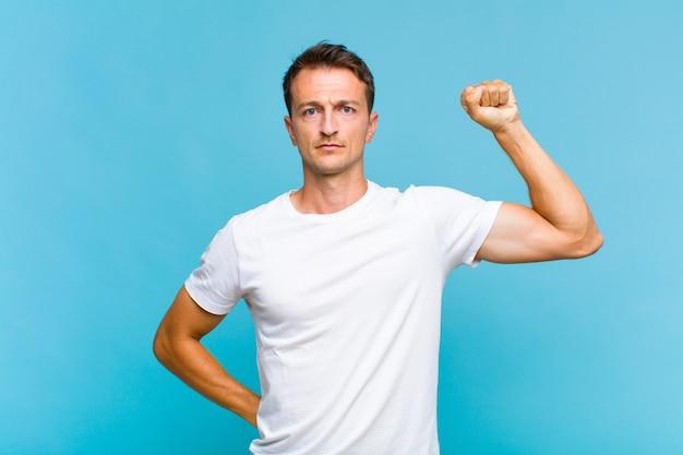 Hombre guapo joven que se siente serio, fuerte y rebelde, levantando el puño, protestando o luchando por la revolución