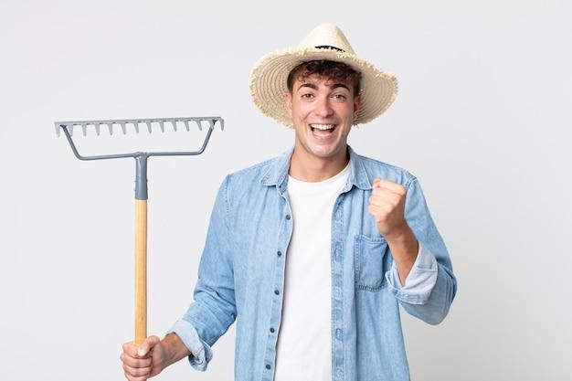 Hombre guapo joven que se siente sorprendido, riendo y celebrando el éxito. concepto de granjero