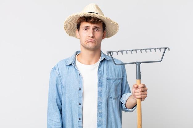 Hombre guapo joven que se siente triste y llorón con una mirada infeliz y llorando. concepto de granjero