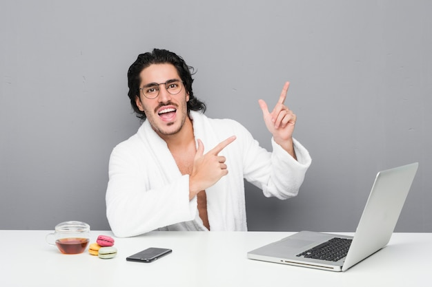 Hombre guapo joven que trabaja después de una ducha señalando con el dedo índice a un espacio de copia, expresando emoción y deseo.