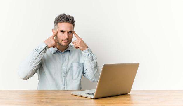 Hombre guapo joven que trabaja con su computadora portátil se centró en una tarea, manteniendo los dedos índice apuntando a la cabeza
