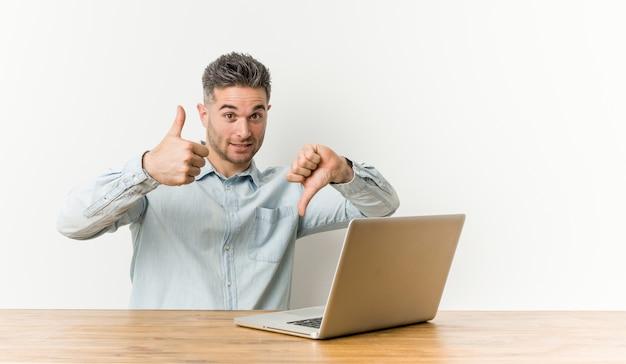 Hombre guapo joven que trabaja con su computadora portátil que muestra los pulgares hacia arriba y hacia abajo, difícil elegir el concepto