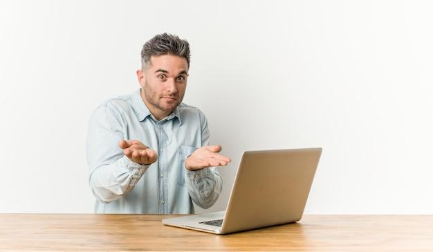 Hombre guapo joven que trabaja con su computadora portátil sosteniendo algo con palmeras