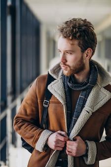 Hombre guapo joven que viaja con bolsa