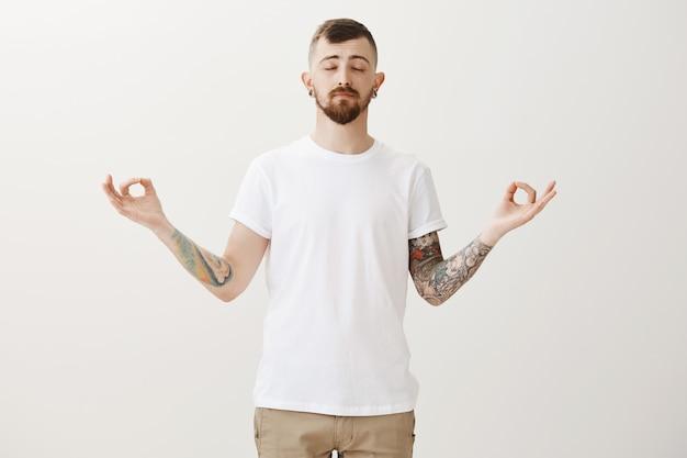 Hombre guapo joven relajado meditando con las manos extendidas en gesto zen