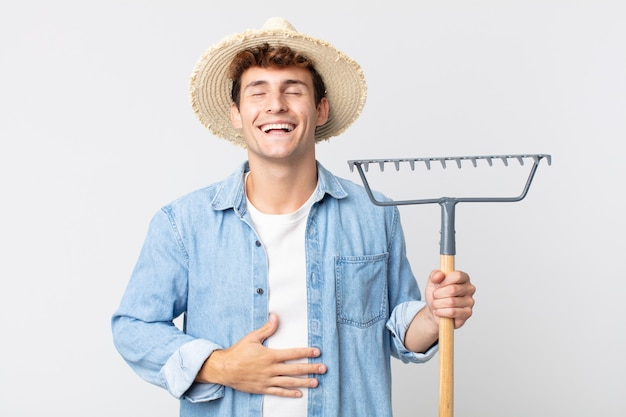 Hombre guapo joven riendo a carcajadas de una broma hilarante. concepto de granjero