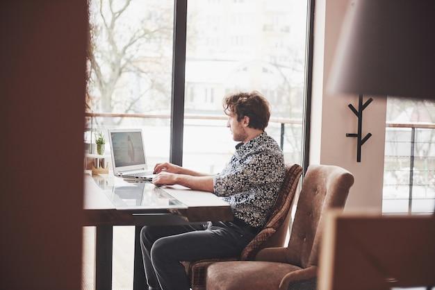 Hombre guapo joven sentado en la oficina con una taza de café y trabajando en un proyecto relacionado con las modernas tecnologías cibernéticas