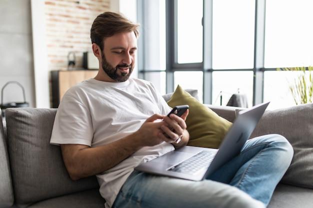 Hombre guapo joven sentado en el sofá en la sala de estar en casa usando la computadora chateando y sosteniendo el teléfono inteligente.