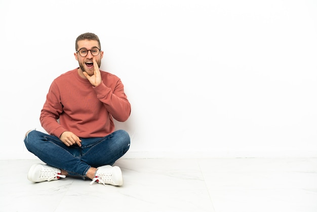 Hombre guapo joven sentado en el suelo gritando con la boca abierta