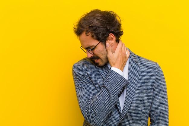 Hombre guapo joven sintiéndose ansioso, enfermo, enfermo e infeliz, sufriendo un dolor de estómago doloroso o gripe contra la pared naranja