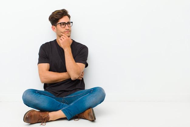 Hombre guapo joven sintiéndose reflexivo, preguntándose o imaginando ideas, soñando despierto y mirando hacia arriba para copiar el espacio sentado en el suelo