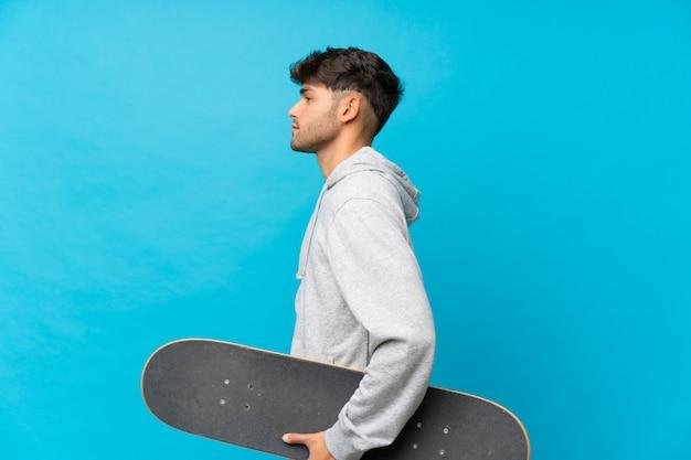 Hombre guapo joven sobre azul aislado con patines en posición lateral