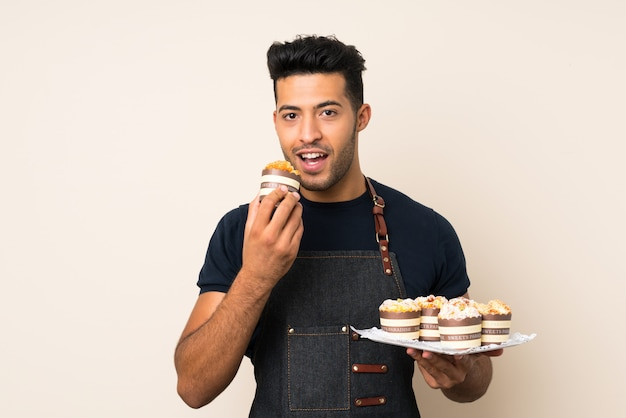 Hombre guapo joven sobre fondo aislado con mini tortas