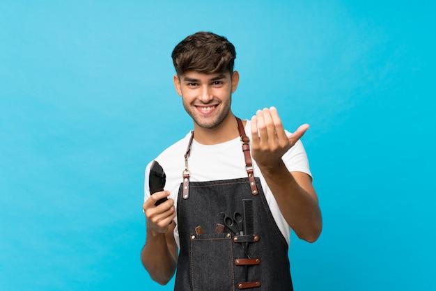 Hombre guapo joven sobre fondo azul aislado con peluquería o vestido de barbero y sosteniendo la cortadora de cabello
