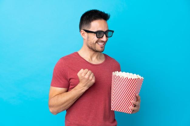 Hombre guapo joven sobre pared azul aislada con gafas 3d y sosteniendo un gran cubo de palomitas de maíz mientras mira hacia el lado