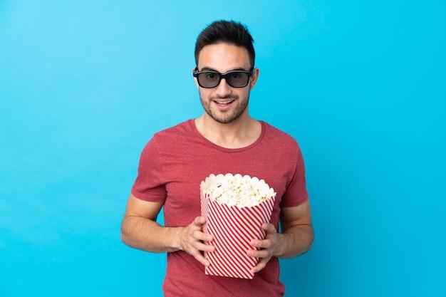 Hombre guapo joven sobre pared azul aislada con gafas 3d y sosteniendo un gran cubo de palomitas de maíz