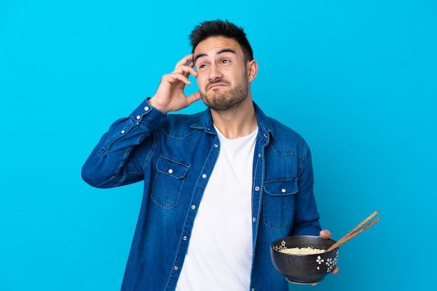 Hombre guapo joven sobre pared azul aislada que tiene dudas y con expresión de la cara confusa mientras sostiene un tazón de fideos con palillos